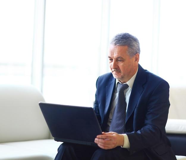 ノートパソコンとオフィスのビジネスマン