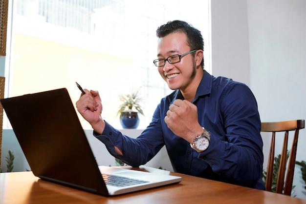 Бизнесмен в чтении хороших новостей онлайн