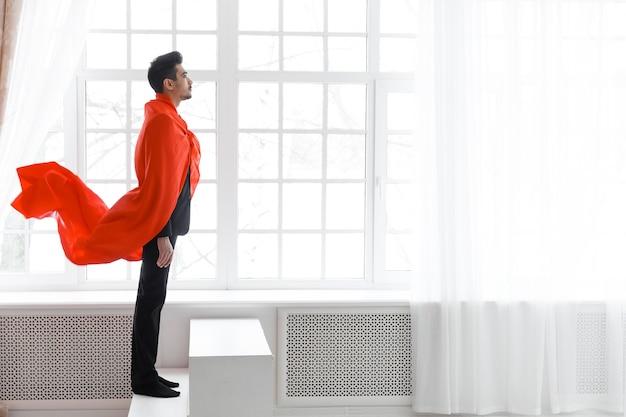 Бизнесмен в красном плаще супергероя. молодой человек в костюме и плаще супермена на лестнице.