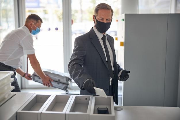 安全マスクと手袋のビジネスマンは、セキュリティゲートを通過するためのボックスにスマートフォンを入れています
