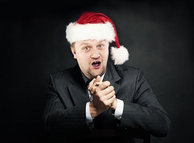 サンタ帽子のビジネスマン。クリスマスと新年のコンセプト。ユーモア。ジャムのためのお金