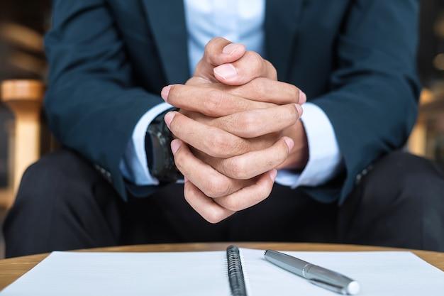 オフィスやカフェでスーツを着たビジネスマン、何か考えている間に握っている男の手。ビジネス、意思決定、ビジョンの概念