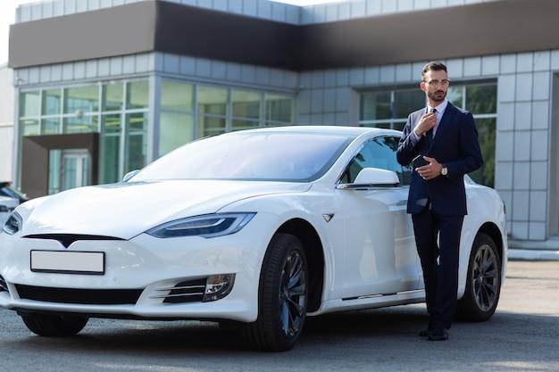 Бизнесмен в костюме. бородатый красивый молодой бизнесмен в темном костюме, стоящий возле белой машины