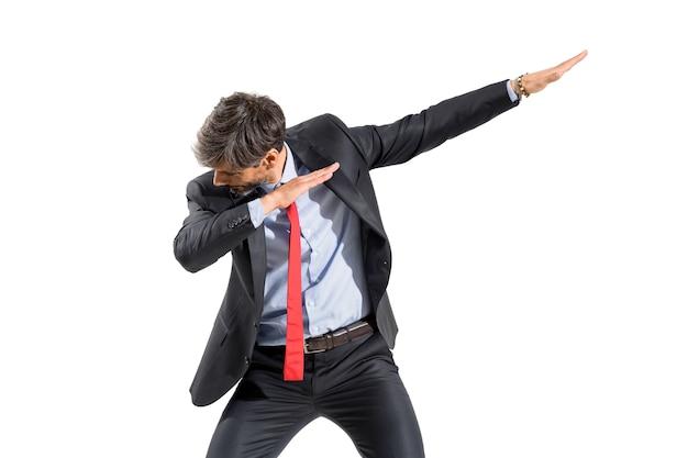 斜めの傾斜した腕と孤立した4分の3の正面の肖像画で頭を下げて軽くたたくダンスポーズをしているスーツのビジネスマン