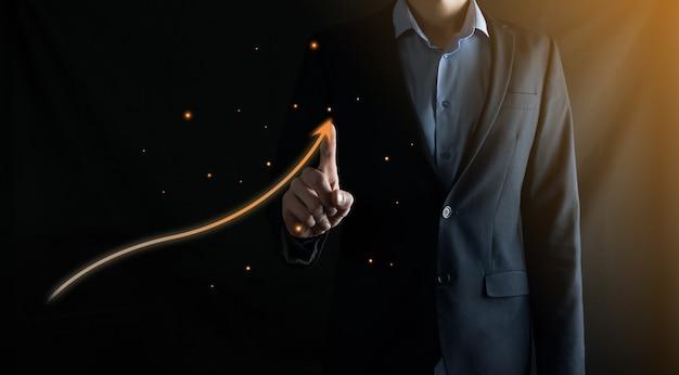 Бизнесмен в костюме рисует пальцем стрелку вверх на черном