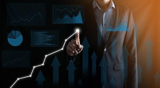 Бизнесмен в костюме рисует его пальцем, указывая стрелку графа.