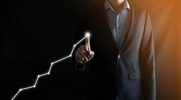 Бизнесмен в костюме рисует пальцем, указывая стрелку на графике