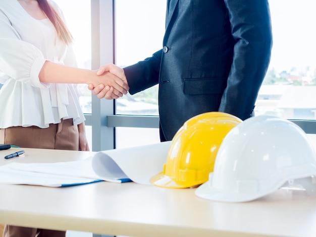 スーツを着たビジネスマン、エンジニアリングまたは建築家と女性が青写真とガラス窓の机の上の黄色と白の安全ヘルメットに握手します。