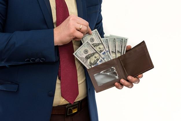 スーツを着たビジネスマンは、孤立した財布から私たちにお金をもらいます。中に米ドルの現金が入った黒い革の財布を持っている男性の手。ビジネス、財務、お金の概念