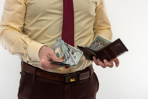 Бизнесмен в костюме достает нам деньги из изолированного бумажника. мужские руки держат черный кожаный бумажник с наличными долларами сша внутри.
