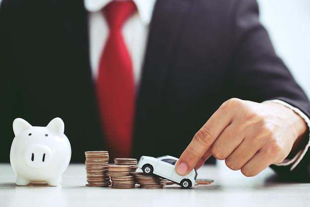 積み重ねられたコインの保険、ローン、購入車の金融コンセプトの貯金箱の貯金箱のたくさんのお金の上に白いおもちゃの車のモデルを持っているスーツのビジネスマン