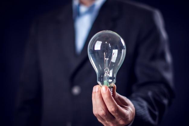 黒の背景の前に手に電球を保持しているスーツの実業家。創造性またはアイデアの概念