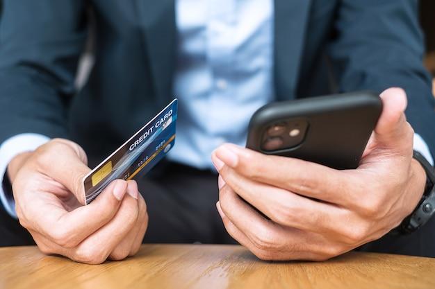 クレジットカードを保持し、カフェやオフィスで注文しながらオンラインショッピングにタッチスクリーンスマートフォンを使用してスーツを着たビジネスマン。ビジネス、テクノロジー、eコマース、オンライン決済の概念