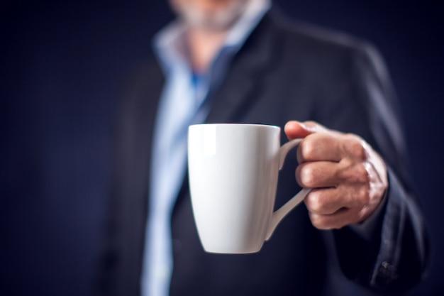 검은 배경 앞에서 차 또는 커피 한 잔을 손에 들고 정장을 입은 사업가. 커피 브레이크 개념