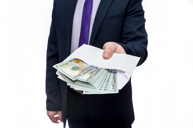Бизнесмен в костюме, держащий конверт с долларовыми банкнотами