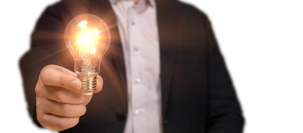 白の革新的な技術と創造性に分離されたアイデア電球を手に持ってスーツの実業家