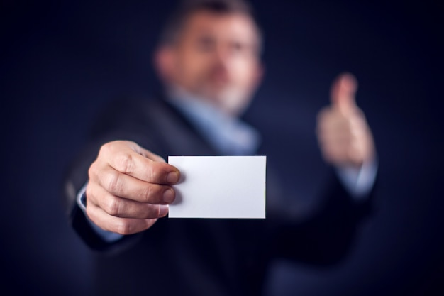 黒の背景の前に名刺を手に持っているスーツのビジネスマン