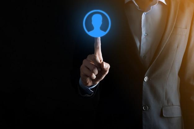 ユーザーの手のアイコンを差し出すスーツの実業家。インターネットアイコンはフォアグラウンドにインターフェイスします。グローバルネットワークメディアコンセプト、仮想画面上の連絡先、コピースペース。