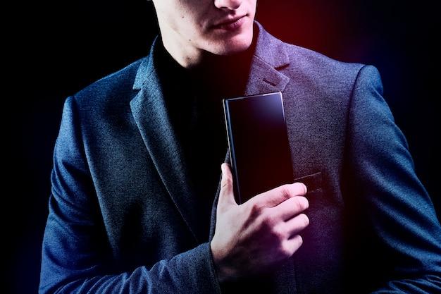 彼のスマートフォンを穴をあけてスーツを着たビジネスマン