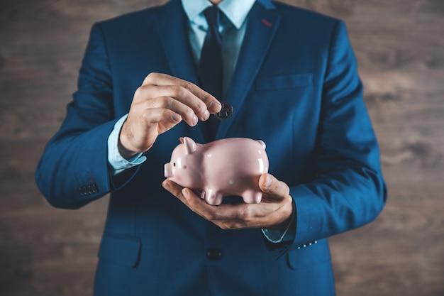 Бизнесмен в костюме держит копилку концепции экономии финансов