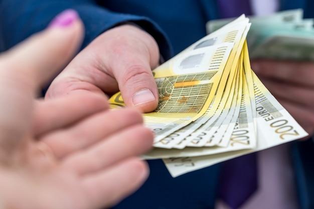 スーツを着たビジネスマンはユーロ紙幣を提供し、クローズアップ