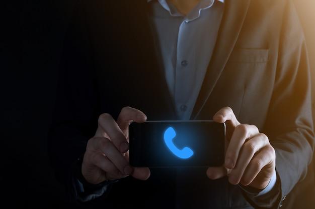黒の背景にスーツを着たビジネスマンが電話アイコンをクリックします。今すぐお電話くださいビジネスコミュニケーションサポートセンターカスタマーサービステクノロジーコンセプト。
