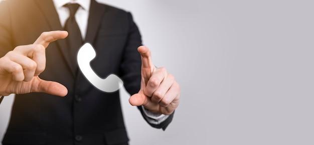검은 배경에 양복을 입은 사업가가 전화 아이콘을 잡고 있습니다. 지금 비즈니스 커뮤니케이션 지원 센터 고객 서비스 기술 개념에 전화하십시오.
