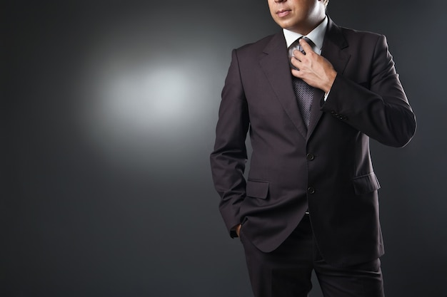 灰色のスタジオの背景にスーツのビジネスマン