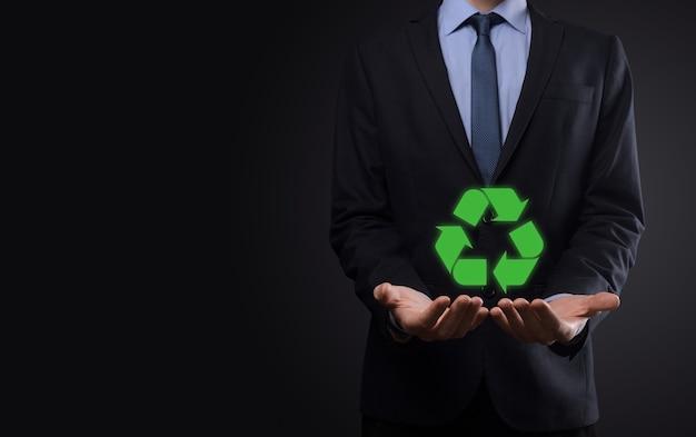 어두운 배경 위에 정장을 입은 사업가가 손에 재활용 아이콘을 들고 있습니다. 생태, 환경 및 보존 개념입니다. 네온 레드 블루 라이트