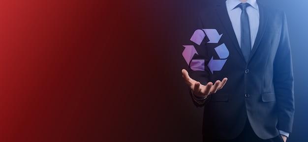 Бизнесмен в костюме на темном фоне держит значок рециркуляции, войдите в его руки. экология, окружающая среда и концепция сохранения. неоновый красный синий свет.