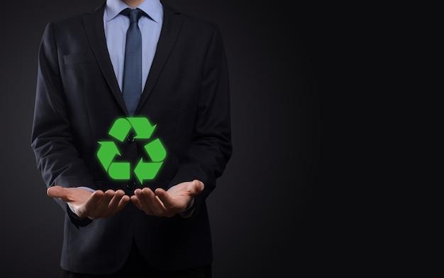暗い背景の上のスーツのビジネスマンは、リサイクルアイコンを保持し、彼の手にサインします。エコロジー、環境、保全の概念。ネオンレッドブルーライト。