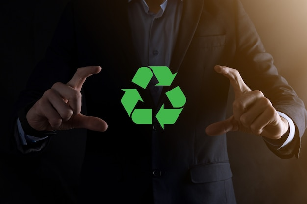 어두운 배경 위에 정장을 입은 사업가가 손에 재활용 아이콘을 들고 있습니다. 생태, 환경 및 보존 개념입니다. 네온 레드 블루 라이트입니다.