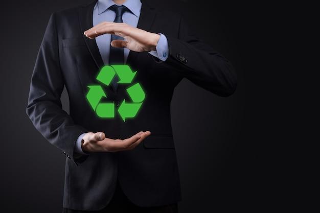 어두운 배경 위에 소송에서 사업가 보유 재활용 아이콘, 그의 손에 서명.