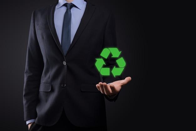Бизнесмен в костюме на темном фоне держит значок утилизации