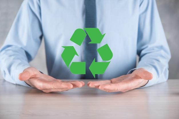 暗い表面にスーツを着たビジネスマンは、リサイクルアイコンを保持し、彼の手にサイン