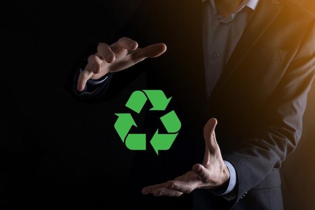 暗い壁にスーツを着たビジネスマンは、リサイクルアイコンを保持し、彼の手にサインします。エコロジー、環境、保全の概念。ネオンレッドブルーライト。