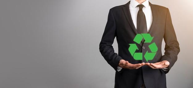 회색 배경 위에 정장을 입은 사업가가 손에 재활용 아이콘을 들고 있습니다. 생태, 환경 및 보존 개념