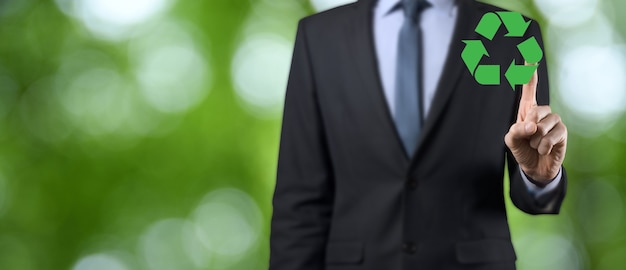 Бизнесмен в костюме на естественном зеленом фоне держит значок рециркуляции, войдите в его руки.