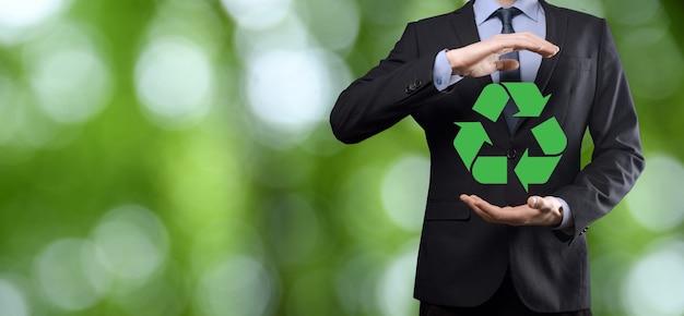 자연 녹색 배경 위에 소송에서 사업가 보유 재활용 아이콘, 그의 손에 서명.