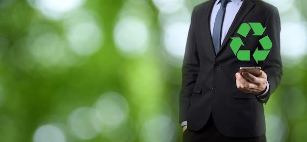 Бизнесмен в костюме на естественном зеленом фоне держит значок утилизации