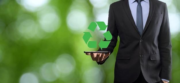 Бизнесмен в костюме над естественным зеленым