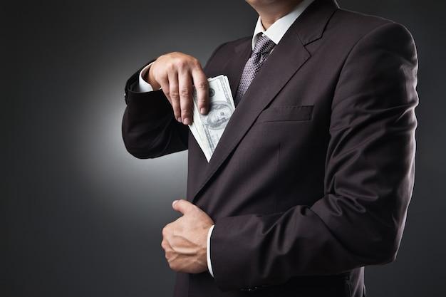 暗い背景に彼のポケットにお金を入れているスーツのビジネスマン