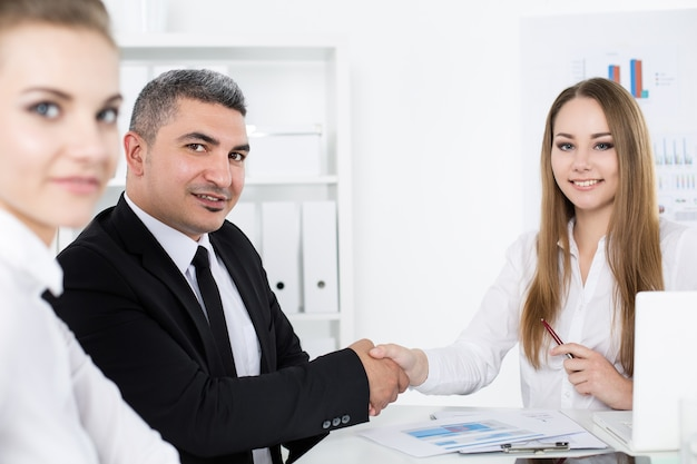 若いビジネス女性の手を振ってスーツのビジネスマン。パートナーは契約を結び、ハンドクラスプで封印しました。正式な挨拶ジェスチャー