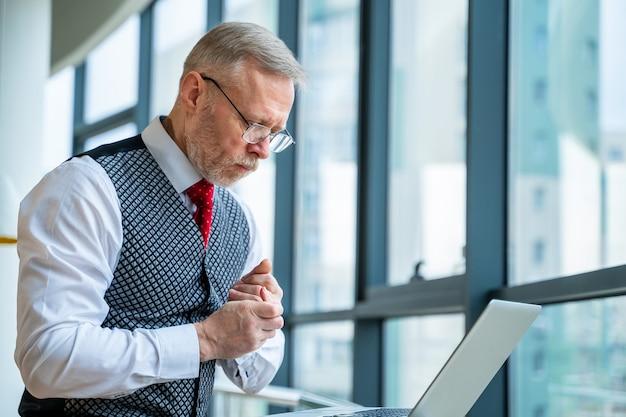 スーツを着たビジネスマン。窓際にノートパソコンを持って座っています。