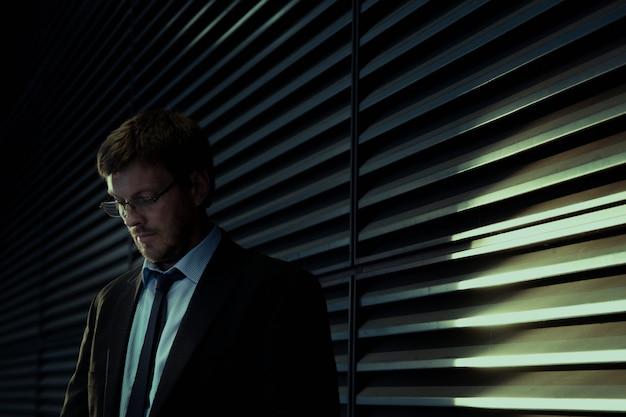 窓の近くに立っているスーツの実業家