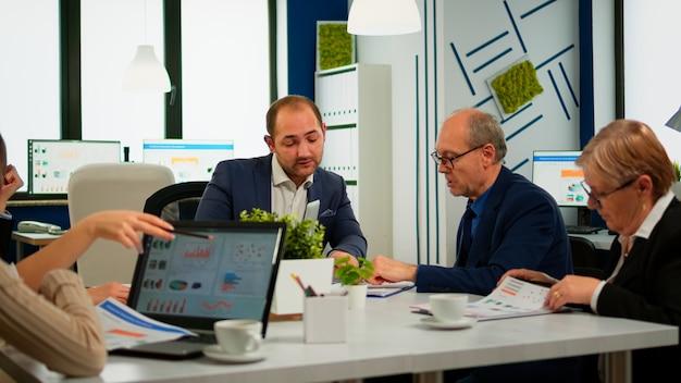 会議のテーブルに座っている多様なビジネスの人々のパートナーと話しているスーツのビジネスマン。ブロードルームとのミーティングでチームワーカーと話し合うプロジェクトリーダー、クライアントと話すグループ交渉