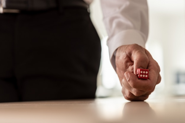 Бизнесмен в костюме бросает красные кости