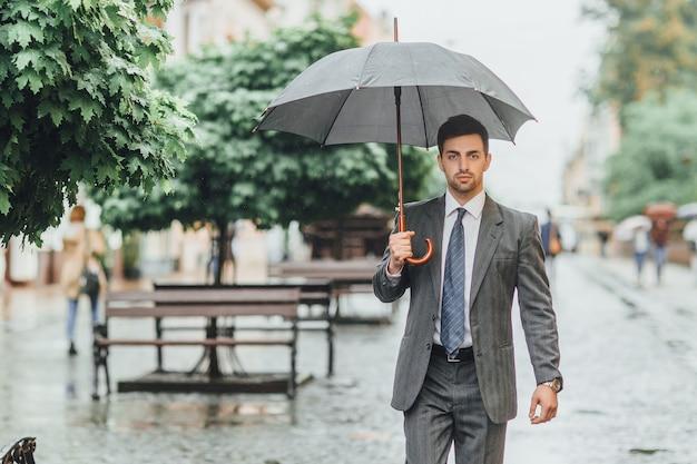 スーツを着たビジネスマンは、緑の木々のある通りを灰色の傘を持って歩き、カメラをのぞき込みます。