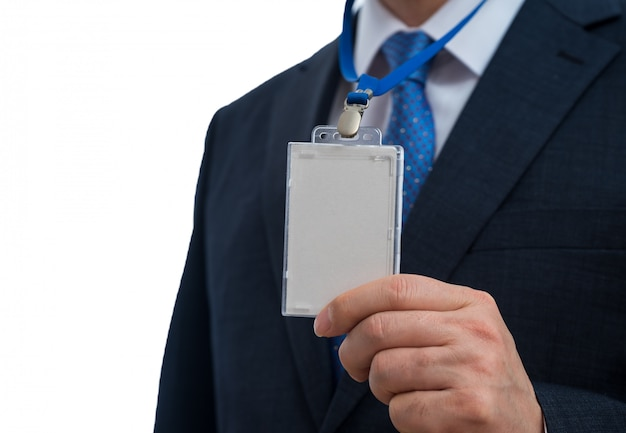 Бизнесмен в костюме нося пустую бирку удостоверения личности или карточку имени на талрепе на выставке или конференции.