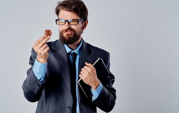 Бизнесмен в костюме с криптовалютой в руке документы монеты биткойн. фото высокого качества
